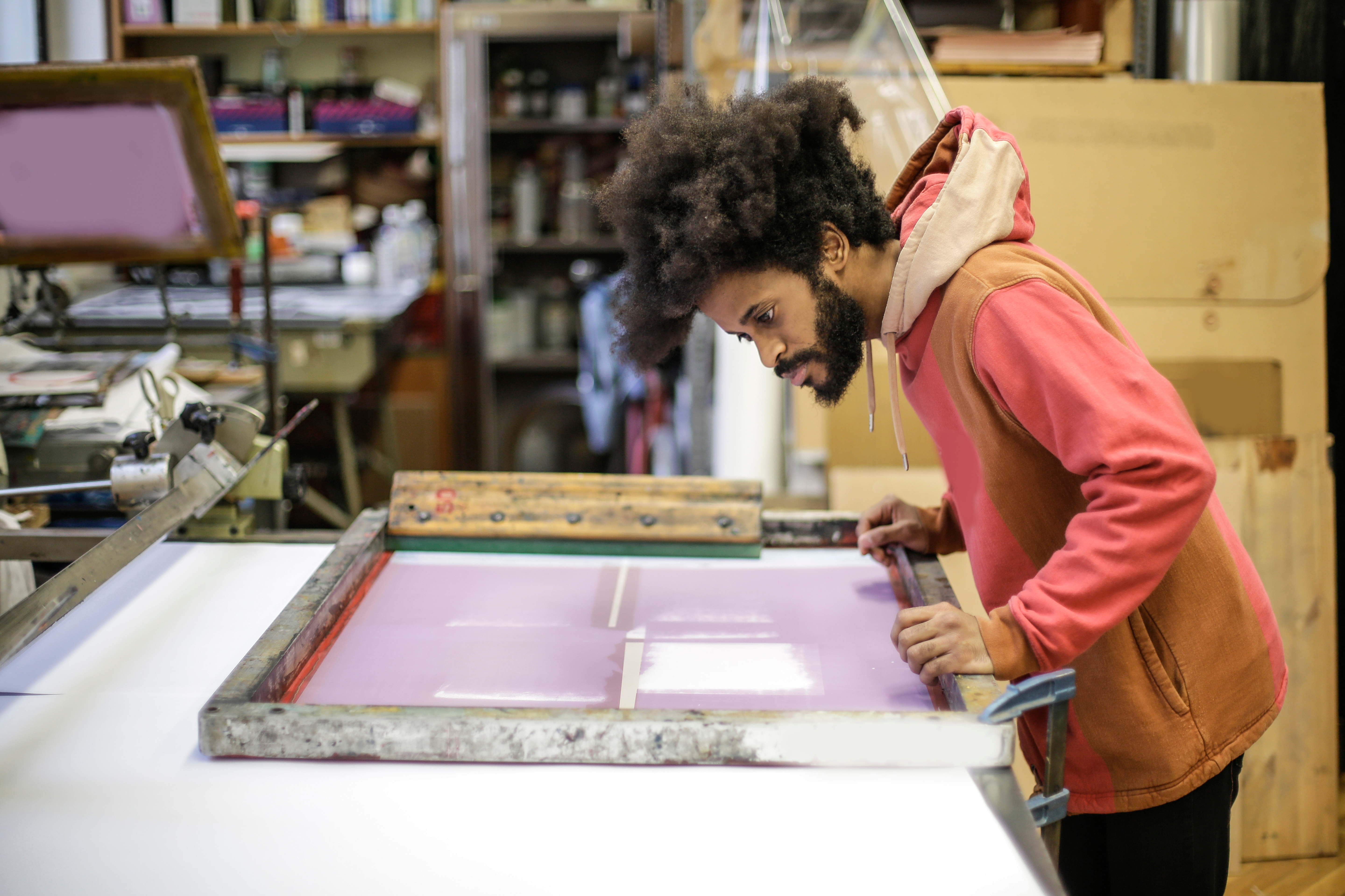 Canva - Creative young ethnic craftsman working with screen printing in workshop